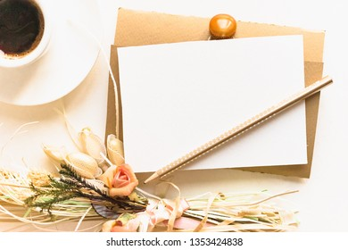 Flatlay elegant composition.Envelope with blank card,pen,bouquet of little roses,cup of coffe.Greeting card mock up.
