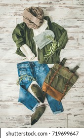 Flat-lay of Fall lady' s clothes outfit. Ecru colored knitted woolen sweater, parka, beige scarf, denim jeans, haki suede boots, backpack, cap over parquet background, top view. Trendy Autumn look