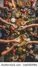 Flat-lay of family clinking glasses over rustic table with Turkish cuisine lamb chops, quince, green bean, vegetable salad, babaganush, rice pilav, pumpkin dessert, lemonade, top view. Middle East
