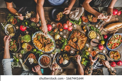 Flat-lay of family feasting with Turkish cuisine lamb chops, quince, bean, vegetable salad, babaganush, rice pilav, pumpkin dessert, lemonade over rustic table, top view. Middle East cuisine - Shutterstock ID 1667441644