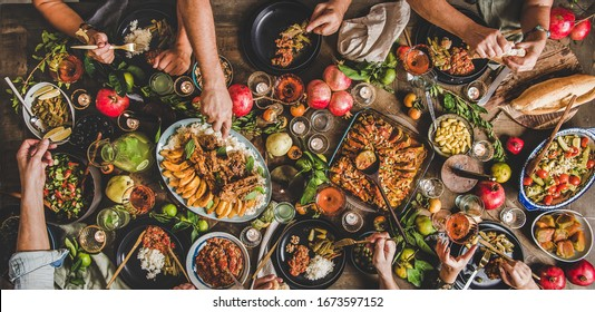 Flat-lay of family feasting with Turkish cuisine lamb chops, quince, bean, vegetable salad, babaganush, rice pilav, pumpkin dessert, lemonade over rustic table, top view, wide composition