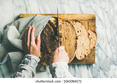 Flat-lay of female hands cutting freshly baked sourdough bread into pieces on rustic wooden chopping board over light grey marble background, top view