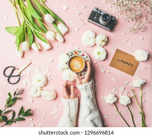 Flat-lay of female hands in knitted sweater holding cup of coffee, scissors, film camera, white tulips and buttercup flowers and sign happy over pink background, top view. Women's Day holiday concept