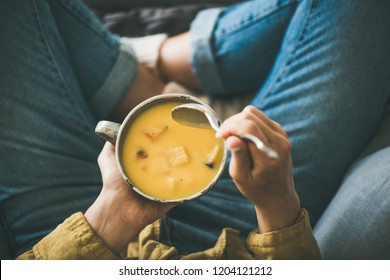 Flat-lay of female in yellow shirt sitting keeping mug of Fall warming pumpkin cream soup with croutons, top view. Autumn vegetarian, vegan, healthy comfort food eating concept