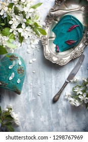 flatlay food background - empty wooden table with blue cheese pieces, white flowers and silver antique dishwear