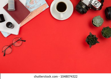 Flatlay frame arrangement with vintage film camera, lenses, glasses,  notebook, map, cup of coffee and succulents. Travel, planning or business mockup, red background, copyspace