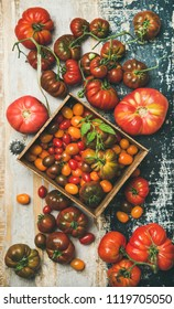Flat-lay of fresh colorful ripe Fall or Summer heirloom, bunch and cherry tomatoes over rustic wooden background, top view. Local market seasonal produce