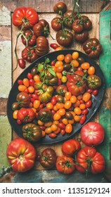 Flat-lay of fresh colorful ripe Fall or Summer heirloom, bunch and cherry tomatoes on plate over painted rustic wooden background, top view, vertical composition. Local market seasonal produce