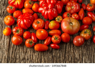 Flat-lay of fresh colorful ripe Fall or Summer heirloom tomatoes variety over rustic background, top view, copy space.