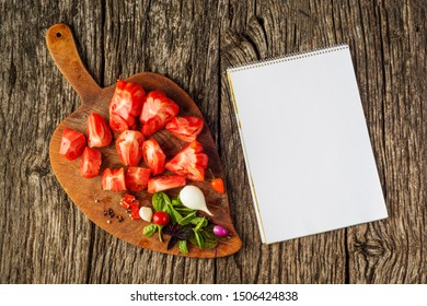 Flat-lay of fresh colorful ripe Fall or Summer heirloom tomatoes variety over rustic tray background with blank paper top view, copy space. Local market seasonal produce