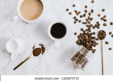 Flatlay of fresh cups of espresso and milk coffee, creamer, coffee beans and spoon on marble background, selective focus