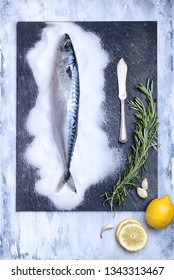 flatlay of fresh fish on a slate stone texture plate decorated with rosemary, garlic, lemon slices, salt and knife. food background with space copy for text