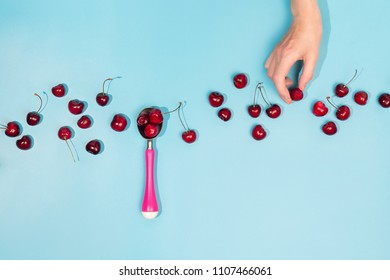 Flatlay with fresh organic cherries in ice cream spoon and woman's hand picking up a berry on blue background