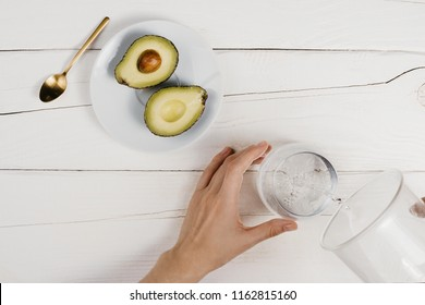 Flatlay with fresh ripe cut avocado halves and woman's hand pouring clean water in a glass on wooden white table, healthy eating concept