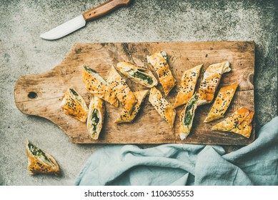 Flat-lay of fresh Turkish borek roll with spinach, feta cheese, black cumin seeds cut in slices on rustic wooden board over concrete background, top view. Traditional East Mediterranean cuisine