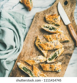 Flat-lay of fresh Turkish borek roll with spinach, feta cheese, black cumin seeds cut in slices on wooden board over marble background, top view, square crop. Traditional East Mediterranean cuisine