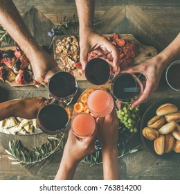 Flat-lay of friends eating and drinking. Top view of people having party, gathering, dinner together sitting at wooden table set with snacks and fingerfoods, square crop. Hands with glasses clinking