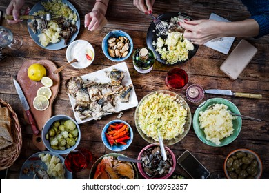 Flat-lay of friends hands eating and drinking together.Food Catering.Buffet Party Concept.having party, gathering,celebrating together at wooden rustic table set with different wine snacks. top view