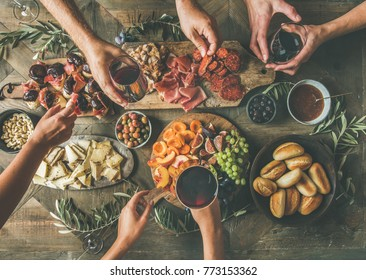Un plat d'amis se donne les mains pour manger et boire ensemble. Vue de dessus de personnes faisant la fête, se réunissant, se célébrant ensemble à une table rustique en bois vintage avec différents snacks de vin et aliments digestifs