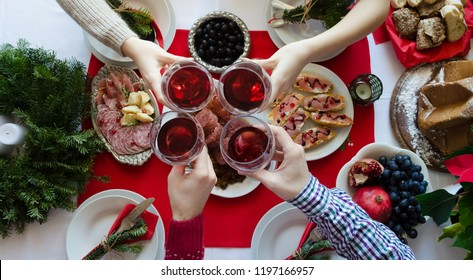 Flat-lay of friends hands toasting with glasses of red wine. Family gathering concept. Traditional Italian Christmas dinner food - lentils with Cotechino, antipasti, Panettone and fruits. Top view.