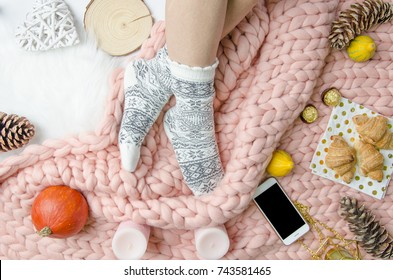 Flatlay Girl legs in a warm socks on background of Merino wool handmade knitted large blanket, trendy concept. Close-up Autumn and winter mood flatly