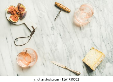 Flat-lay of glass of rose wine with ice cubes, cheese and fresh figs over marble background. Summer wine and snack set, top view, copy space