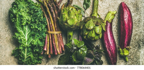 Flat-lay of green and purple fresh vegetables over concrete background, top view. Local seasonal produce for healthy cooking. Eggplans, green beans, kale, asparagus, artichoke, basil. Clean eating