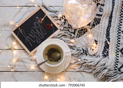 "Flatlay with green tea in white cup, blackboard with handwritten text ""hygge"", heart shaped lantern and many small light, knitted blanket on wooden table"
