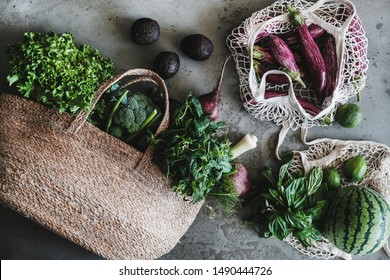 Flat-lay of of grocery jute and net bags full of fresh vegetables, greens, fruit from local farmers market over grey concrete background. Zero waste, healthy, eco-friendly, vegan, clean eating concept