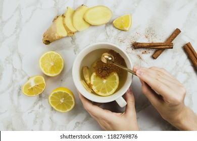 Flatlay of healthy drink with lemon, fresh ginger root, cinnamon sticks and agave syrup on marble background, natural cold or sore throat