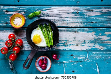 Flat-lay of healthy vegetarian breakfast with fried eggs and green aspargus in vintage cast iron pan on turquoise vintage table from above. Clean eating, diet food concept