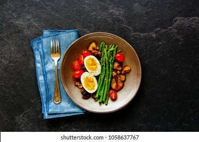 Flat-lay of healthy vegetarian breakfast plate. Aspargus, tomatoes, mushrooms and eggs over black stone copy space background. Energy boosting food concept. Top view.