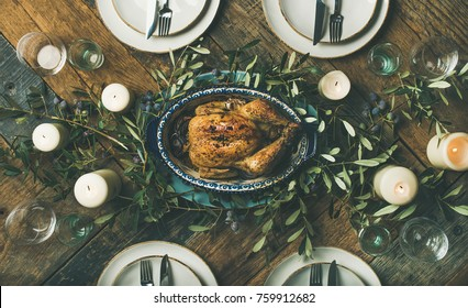 Flat-lay of holiday table setting for party or celebration with roast chicken, candles and olive branches over rustic wood table background, top view. Christmas, New year, Thanksgiving dinner concept