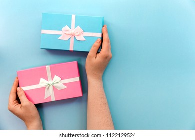 Flatlay holidays giftbox present in woman hands on the pastel blue background for holiday, christmas, birthday party