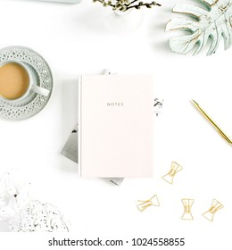 Flatlay of home office desk table. Workspace with pale pastel pink notebook and decorations on white background. Flat lay, top view. Woman home office.