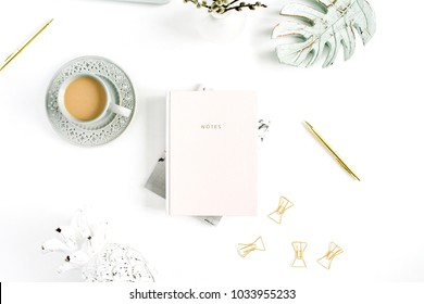 Flatlay of home office desk table. Workspace with pale pastel pink notebook and decorations on white background. Flat lay, top view.