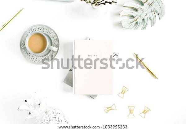 Flatlay van kantoor bureau aan huis tafel. Werkruimte met lichtroze notitieboekje en decoraties op een witte achtergrond. Plat lag, bovenaanzicht.