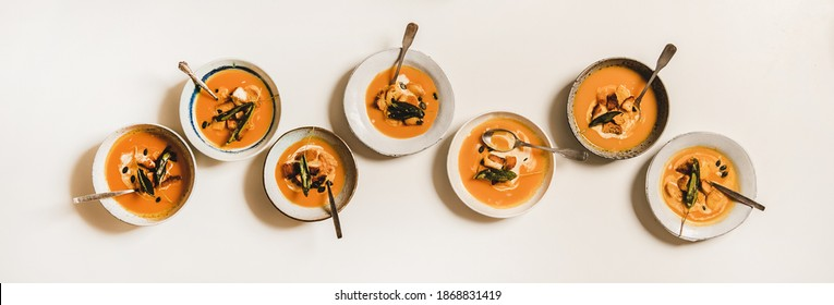 Flat-lay of homemade fall pumpkin cream soup in plates with sour cream, pumpkin seeds and bread croutons over plain white table background, top view. Healthy comfort food and clean eating - Shutterstock ID 1868831419
