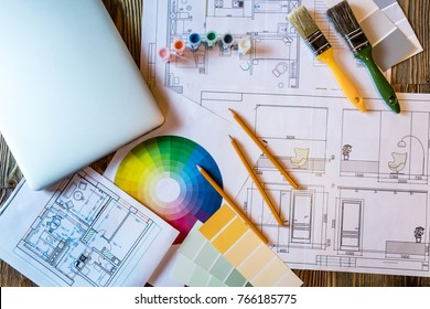 Flatlay interior design with laptop and colour circle diagram, plans and art tools