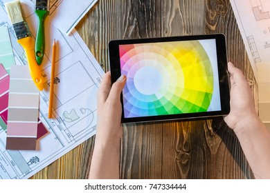 Flatlay interior designer with pad and colour circle, plans and art tools