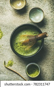 Flat-lay of Japanese tools for brewing matcha tea. Matcha powder in tin can, Chashaku spoon, Chasen bamboo whisk, Chawan bowl and cups for ceremony over concrete background, top view