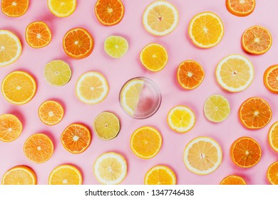 Flatlay of lemon water on pink background with various sliced citrus fruits on side