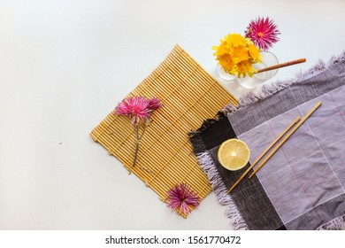 flatlay of a mat, lemon, echinacea on a white surface