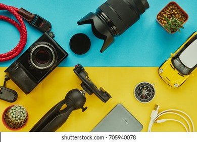 Flatlay with mirrorless camera, lens, car mockup, power bank, and tripod, Top view work table for photographer or traveller