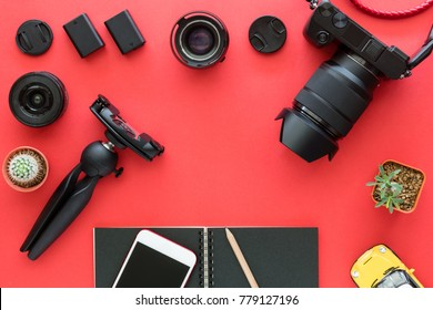Flatlay of Mirrorless Camera, Lenses, Cleaning set And Accessories on red background as top view of Creative Gear for photographer, traveller and blogger