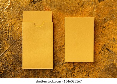 Flatlay mockup of golden foil blank business card and a cardholder at golden textured background.