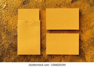 Flatlay mockup of two golden foil blank business cards and a cardholder at golden textured background.