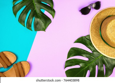 Flatlay with monstera leaves, straw hat and other accessories, summer and holiday concept, copyspace