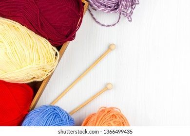 Flatlay of multicolored pastel knitting skeins of yarn and knitting needles on a white background