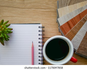 Flat-lay on blank notepad and hot coffee for interior designer working for vinyl floor8ng design idea